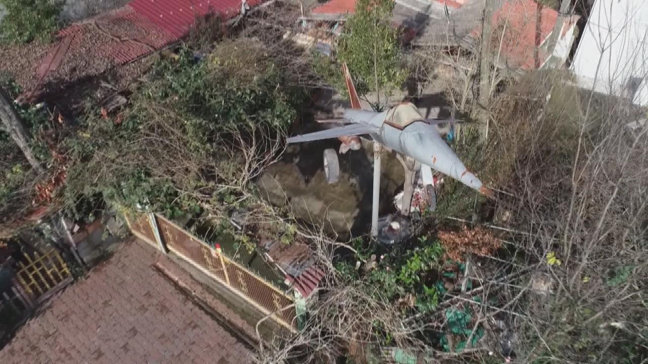 Düşen savaş uçağını evinin önünde sergiliyor